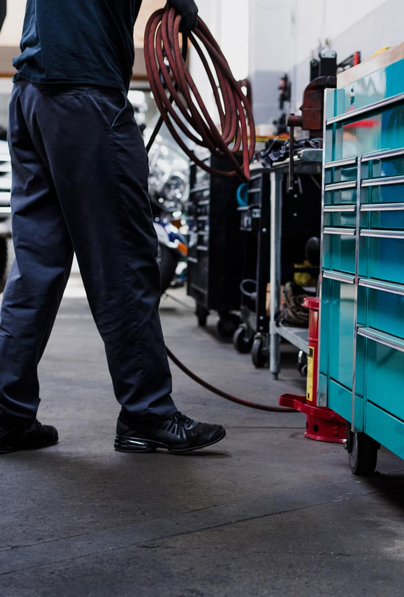 A person coiling hose walking towards a tool chest.