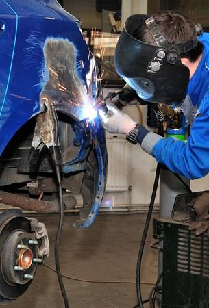 Worker welding a car body.